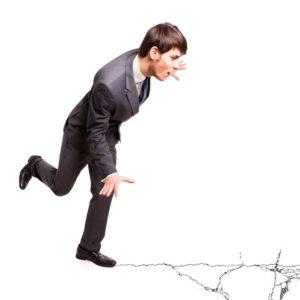 38469876 - businessman balancing on cracking ground